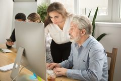 stock image of  female executive teaching senior office worker helping explainin
