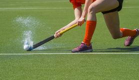 stock image of  female field hockey player passing to a team mate on a modern, water artificial astroturf field