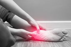 stock image of  female foot heel pain with red spot, plantar fasciitis