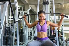 stock image of  female in gym. sport, fitness, bodybuilding, woman exercising and flexing muscles on machine in gym. asian girl. asian girl
