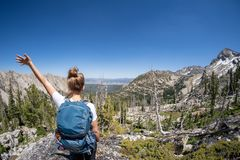 stock image of  female hiker with backpack along the sawtooth lake trail in idaho. back facing camera. concept for solo female travel and hiking