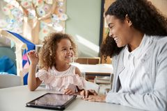 stock image of  female infant school teacher working one on one in a classroom using a tablet computer with a young mixed race schoolgirl, smiling