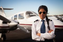 stock image of  female pilot waiting in front of her aircraft