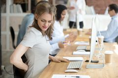 stock image of  female suffering from low back pain at work