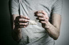 stock image of  the fight against drugs and drug addiction topic: addict holding package of cocaine in a gray t-shirt on a dark background