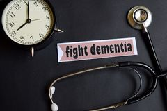 stock image of  fight dementia on the paper with healthcare concept inspiration. alarm clock, black stethoscope.