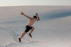 stock image of  fit man running fast on the sand. powerful runner training outdoor on summer.
