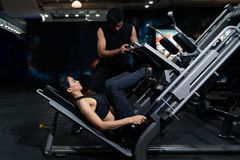 stock image of  fit woman working out with trainer at the gym, woman doing muscle training at the gym. athlete working out at the gym by pulling w