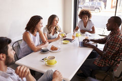 stock image of  five adult friends sitting in a cafe, elevated view close up