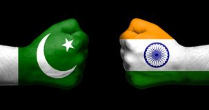 stock image of  flags of india and pakistan painted on two clenched fists facing