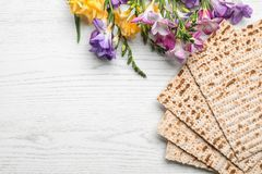 stock image of  flat lay composition of matzo and flowers on wooden background. passover pesach seder