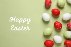 stock image of  flat lay composition with painted eggs and text happy easter