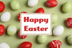 stock image of  flat lay composition of painted eggs and text happy easter