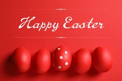 stock image of  flat lay composition of red painted eggs and text happy easter