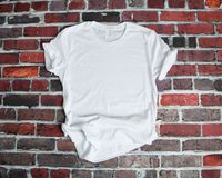 stock image of  flat lay mockup of white tee shirt on brick background