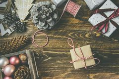 stock image of  flat lay on rustic aged wood background, christmas or new years gits wrapped in craft brown white paper. ribbon,twine,pine cones