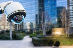 stock image of  security cctv camera or surveillance system with buildings on blurry background