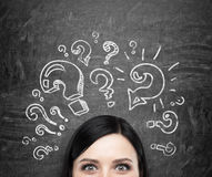 stock image of  a forehead of the girl who is pondering about unsolved problems. question marks are drawn around the head. black chalkboa
