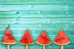 stock image of  four watermelon slice popsicles on blue wood background with copy space, summer fruit concept