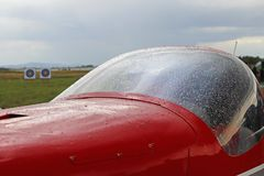 stock image of  fragment of a light two-seater sports airplane in raindrops. exhibition, competitions and airshow. hobbies and free time. festival
