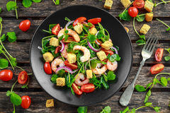 stock image of  fresh healthy prawns salad with tomatoes, red onion on black plate. concept healthy food