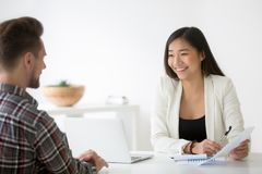 stock image of  friendly asian hr smiling talking to candidate at job interview