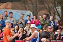 stock image of  front view of public heads contemplate city marathon runners.