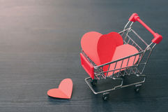 stock image of  full of hearts in the shopping cart on wooden floor