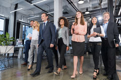 stock image of  full length business people team walking in modern office, confident businessmen and businesswomen in suits diverse with
