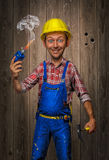 stock image of  funny craftsman with hammer, cordless screwdriver and helmet