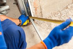 stock image of  garage door installation. worker use a ruler to verify correct installation of metal profile.