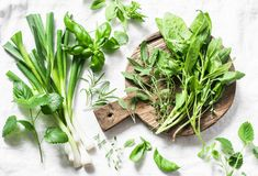 stock image of  garden herbs - spinach, basil, thyme, rosemary, sage, mint, onion, garlic on a light background, top view. fresh food ingredients