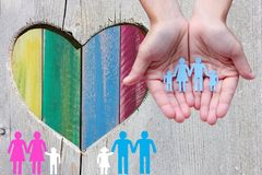 stock image of  gay and lesbian families on wooden background with multicolor rainbow heart