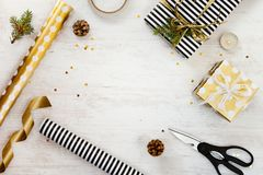 stock image of  gift boxes wrapped in black and white striped and goden dotted paper with, pine, cones, candle and wrapping materials on a white w