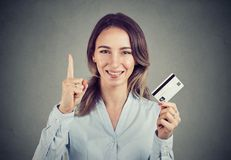 stock image of  girl with credit card holding finger up