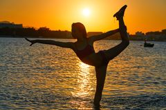 stock image of  girl gymnastics pose at sunset beach