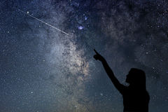 stock image of  girl looking at the stars. girl pointing a shooting star.