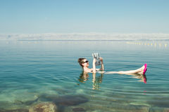 stock image of  girl reading newspaper floating on surface dead sea enjoy summer sun and vacation. recreation tourism, healthy lifestyle, free tim