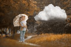stock image of  a girl walking the rainy cloud at autumn time on the orange background