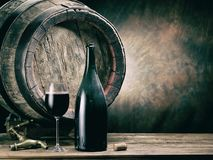 stock image of  glass of red wine and wine bottle. oak wine keg at the background.