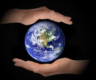 stock image of  glowing earth globe in hands on black background, environment concept, elements of this image furnished by nasa