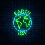 stock image of  glowing neon sign of world earth day with globe symbol and greeting text on dark brick wall background.