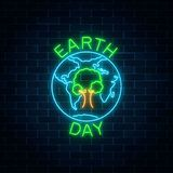 stock image of  glowing neon sign of world earth day with tree in globe symbol and greeting text on dark brick wall background.
