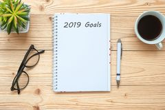 stock image of  2019 goals with notebook, black coffee cup, pen and glasses on table, top view and copy space. new year new start, resolution, sol