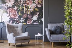 stock image of  golden pendant light above a cozy armchair in a fancy living room interior with molding and floral print on gray walls
