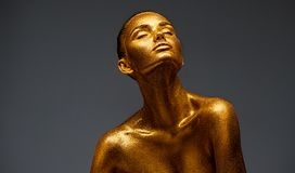 stock image of  golden skin beauty woman portrait. fashion girl with holiday golden makeup. body art