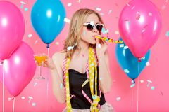 stock image of  gorgeous trendy young woman in party outfit celebrating birthday. party mood, balloons, flying confetti, cocktail and dancing.