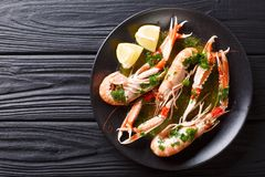 stock image of  gourmet seafood scampi or langoustine or norway lobster are served on a black plate with sauce and lemon. horizontal top view