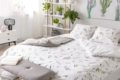 stock image of  green plant pattern on white bedding and pillows on a bed in a nature loving bedroom interior