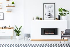 stock image of  grey armchair next to fireplace under poster in living room interior with plant and stool. real photo